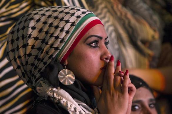 A Palestinian woman watches a public screening of Palestinian President Mahmoud Abbas' speech at the United Nations, in the West Bank city of Ramallah September 23, 2011. (Credit: Reuters/Darren Whiteside)