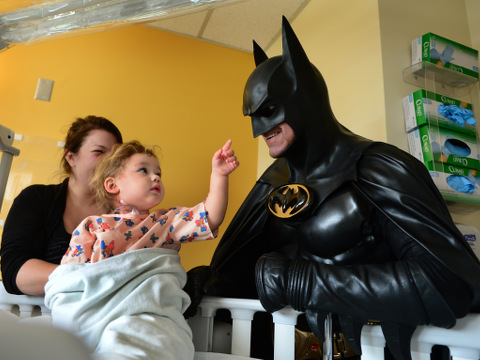 Leonard Robinson, dressed as Batman, visits Mattie Dillon on the pediatrics floor of Charleston Area Medical Center Women and Children's Hospital in Charleston, West Virginia, August 15, 2015, two days before the Maryland man who delighted thousands of children by impersonating Batman at hospitals and charity events died when he was hit by a car while standing in the fast lane of Interstate 70, checking the engine of his custom-made Batmobile (Credit: AP Photo/The Charleston Gazette/Kenny Kemp)